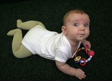 Baby on carpet. Blue eyed baby on a carpet royalty free stock images