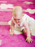Baby on carpet Stock Images