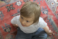 Baby on carpet. A little boy sitting on a carpet Royalty Free Stock Images