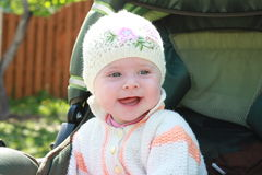Baby in the carriadge. Smilling baby in knitted capand blouse seat in a carriadge Stock Images