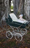 Baby in carriage. Happy baby girl sitting a stroller under a tree Stock Photo