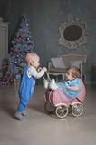 Baby carriage, baby boy ang girl. Little boy playing with a little girl Royalty Free Stock Photos