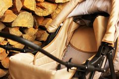 Baby carriage on the background of stacked firewood stock images