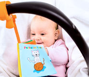 Baby carrier. Baby playing with story book sitting in baby carrier Royalty Free Stock Photo