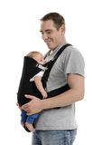 Baby carrier. Father carrying his baby in sling carrier Royalty Free Stock Images