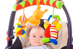 Baby carrier and toys. Baby playing in baby carrier. Toys are property released Royalty Free Stock Images