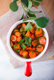 Baby carrots cooked with garlic. Honey and parsley Stock Photos