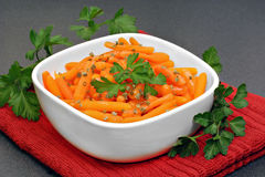Baby carrots garnished with parsley in a white bowl. Stock Photos