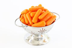 Baby Carrots in a Miniature Colander. On a white background royalty free stock image
