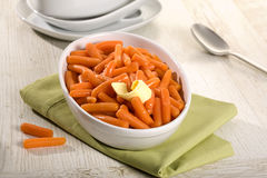Baby carrots in white bowl on table Stock Photo
