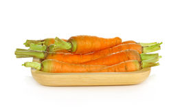 Baby carrots in wooden plate on white background Royalty Free Stock Photo