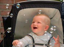 Baby Catching Bubbles. Baby in Carriage trying to catch soap bubbles Royalty Free Stock Image