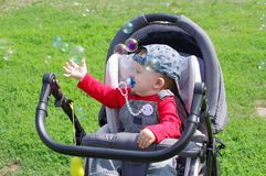 Baby catchs soap bubbles. Baby age of 10 months catchs soap bubbles Stock Photos