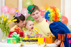 Baby celebrating first birthday with parents and clown Stock Image
