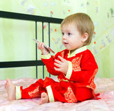 Baby with cell phone in festive costume sitting on the bed. At home Stock Photos