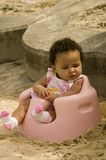 Baby in a chair. A baby girl sitting in a baby chair on a sandy beach Stock Images
