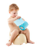 Baby on the chamber pot with toilet paper. Funny baby sitting on the chamber pot and playing with toilet paper, isolated on white royalty free stock image