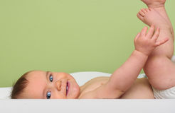 Baby on change table. Happy baby smiling on change table with copyspace Royalty Free Stock Photo