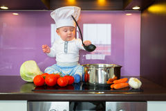 Baby chef cooking in the kitchen. Little baby boy cook in chef hat at the kitchen Stock Photography