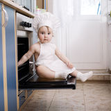 Baby chef cooks in the oven food stock photos