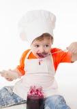 Baby chef eating jam isolated on white background Stock Photography