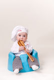 Baby in a chef Outfit. Sitting on a chair holding and chewing cooking utensil Royalty Free Stock Photo