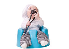 Baby in a chef Outfit. Sitting on a chair holding and chewing cooking utensil Royalty Free Stock Image