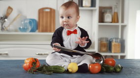 Baby chef sitting with ladle and vegetables stock video