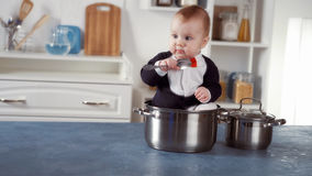 Baby chef sitting in a pot. On the kitchen background Stock Image