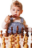 Baby and Chess. Baby girl behind chess desk holding a chess piece in her hand and trying to taste it. Isolated on white background stock photo