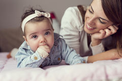 Baby chewing her hands Stock Images