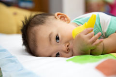 Baby chewing on teething plastic toy. Portrait of sweet baby. Baby chewing on teething plastic toy Stock Images