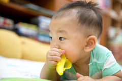 Baby chewing on teething plastic toy. Portrait of sweet baby. Baby chewing on teething plastic toy Stock Image