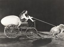Baby chick pulling cart with woman and giant egg Royalty Free Stock Photos