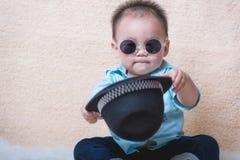 Baby child boy fashion. Sitting with sunglasses royalty free stock image