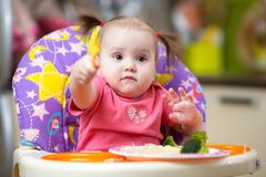 Baby child eating in chair Royalty Free Stock Images