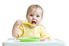 Baby child eating healthy food with a spoon Stock Photo