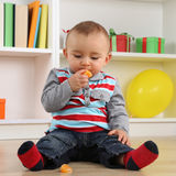 Baby child eating mandarin orange fruit Stock Image