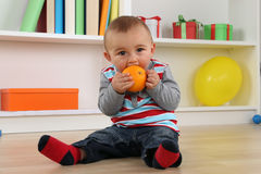 Baby child eating orange fruit Royalty Free Stock Photography