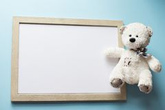 Baby , child frame and white teddy bear on blue background.  stock image