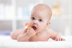 Baby child lying on belly weared with teether in mouth Stock Image