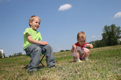 Baby and child on meadow royalty free stock images