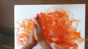 Baby child is painting with hands using colored finger gel paints, heart shape