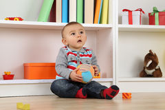 Baby child playing with ball and looking up Royalty Free Stock Images