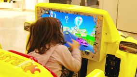 Baby child racing game arcade drive. Baby child play racing arcade drive game in a mall in Bologna, Italy, 08 March 2019 stock video footage