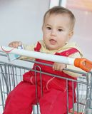 Baby child in shopping cart in supermarket Stock Image