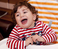 Baby child sits in a children's chair laughing rejoices Royalty Free Stock Image
