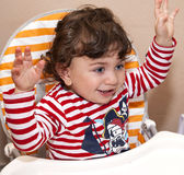 Baby child sits in a children's chair laughing rejoices Royalty Free Stock Photos