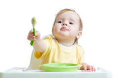 Baby child sitting in chair and outstretching a Stock Photography