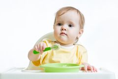 Baby child sitting in chair with a spoon Royalty Free Stock Photos